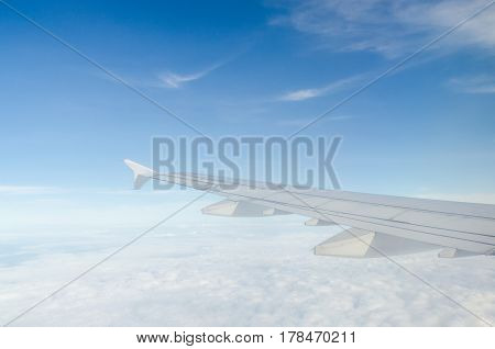 Wing of airplane flying above the cloud
