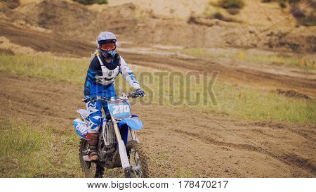 Young woman mx biker - motocross racer on dirt bike at sport track, telephoto