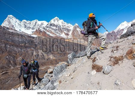 Group of Hikers with Backpacks and high Altitude climbing Gear walking up on steep Footpath snowy Summits View on Background