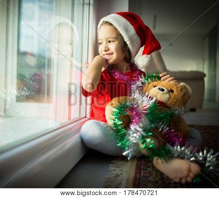 Children playing with Teddy bear as Santa Claus at home