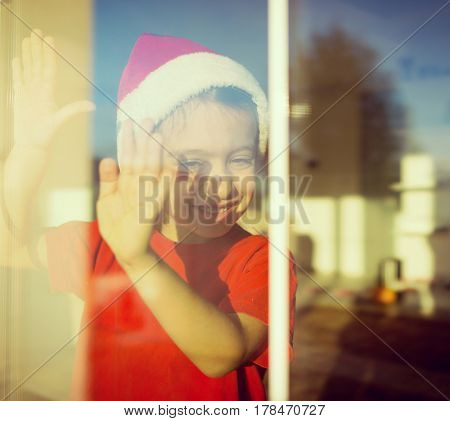 Child waiting for coming of Santa and Christmas and New Year on his window at beautiful home