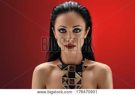 Devilish beauty. Studio portrait of a gorgeous dark haired young woman wearing red lipstick and dark eye shadow looking to the camera confidently on red background confidence elegance femininity