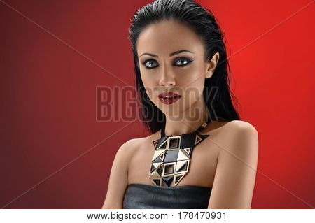 Graceful young lady. Shot of a beautiful sexy young brunette woman in a black leather dress wearing professional makeup with smoky eyes and red lipstick posing on red background copyspace