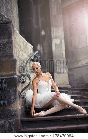Passion in every curve. Shot of a stunning ballerina resting near on old castle on the stairs