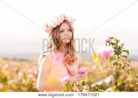 Smiling teenage girl 14-16 year old wearing pink dress and floral wreath with roses standing in rose field.