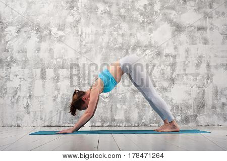 Young attractive woman wearing sportswear doing yoga. Fit girl exercising on blue mat against grey wall indoors.