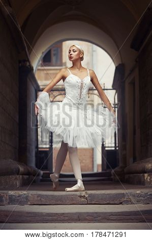 Perfect pirouette. Portrait of a stunning ballerina walking through the archway
