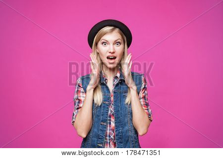 Surprised hipster young woman wearing black hat and denim vest shcoked. isolated on pink stusio background