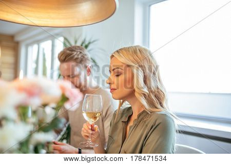 Young and attractive blonde woman enjoying a glass of wine.
