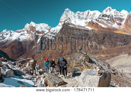 Group of Hikers and Nepalese Porter carrying many household and camping Items on popular touristic trek to high altitude Mountain