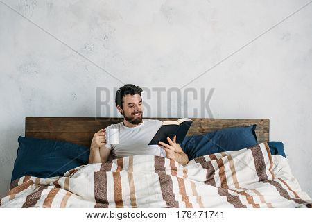 Bearded man reading a big book lying in his bedroom. Young guy holding paperback and being under the blanket. He is enjoying with story