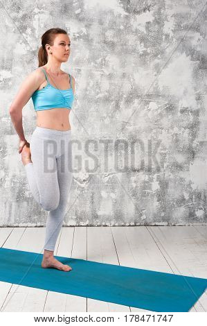 Full length portrait of young caucasian woman practicing yoga indoors. Sporty girl wearing sportswear exercising on blue mat.