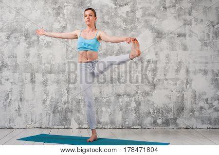 Flexible woman wearing sportswear practicing yoga on blue mat.