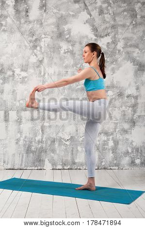 Yoga practice indoors. Young flexible girl exercising on blue mat against grey wall.