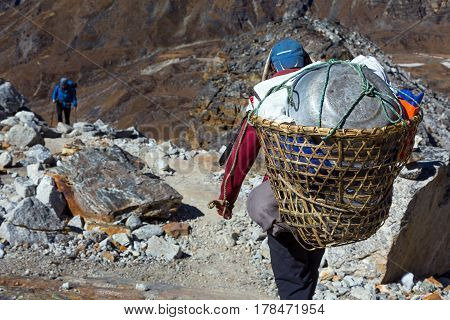 Nepalese Porter carrying traditional handmade Basket with rural household goods using head strap on Mountain Footpath rear view