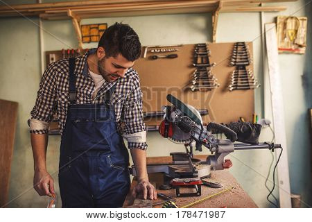Young carpenter working in his work shop.