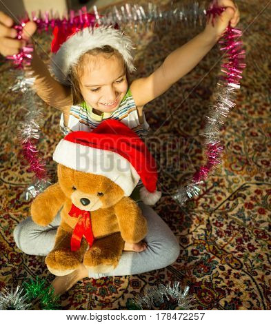 Little boy with his cute Teddy bear waiting for Santa Claus at home window on Christmas eve