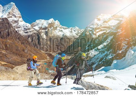 Group of Friends in sporty Outwear using climbing Gear traversing Glacier against Mountain Panorama with high Peaks and Valley Lakes towards rising Sun