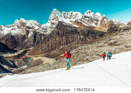 Mountain Climbers Team led by young Man in red Jacket moving on snowy Glacier with majestic top View of Valley with blue Lakes and sharply pointed Peaks on Background.