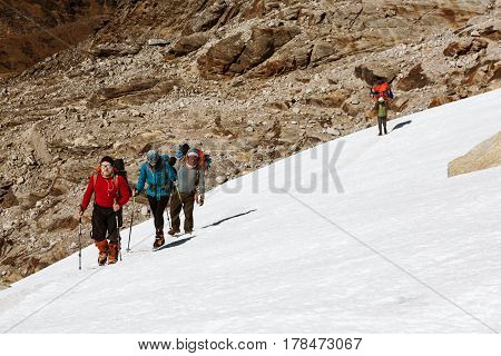 Group of Climbers with Backpacks and climbing Gear in protective windproof Clothing walking on Snow Slope Nepalese Porter using traditional Head Strap with Basket on Background.