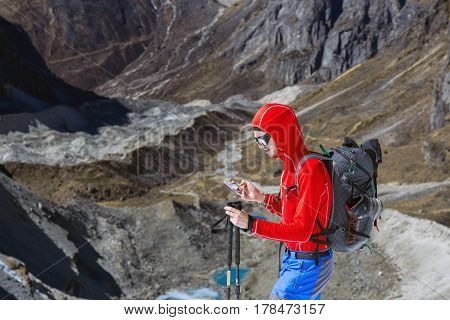 Young smiling Alpine Climber in red Jacket and blue Pants using modern smart Phone in high Mountains