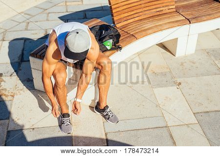 Photo from above of an athletic man taking a break from workout while tying his shoes and sitting on a bench.