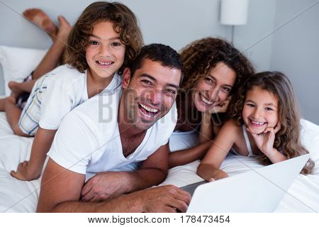 Portrait of family using laptop together on bed in bedroom