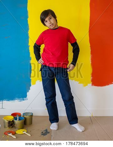Child helping painting wall at home