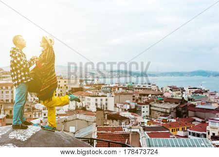 Love Story Man and Woman holding Hands staying on Top of Building Roof with Bird Flight View of City with Sun shining