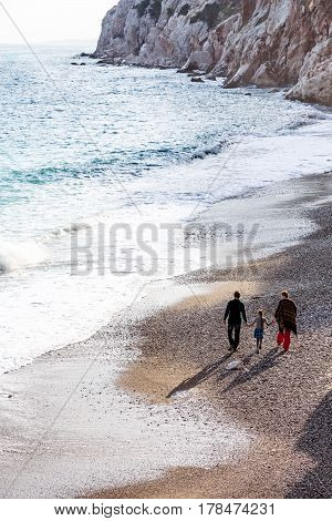 Family of three People Mother Father and baby Daughter walking together on Ocean Beach with beautiful Sea Surf