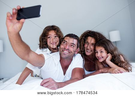 Happy family taking a selfie on bed in bedroom