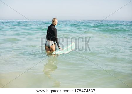 Woman in wetsuit holding a surfboard on the beach at sunny day