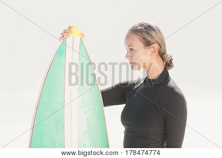 Woman in wetsuit holding a surfboard on a sunny day