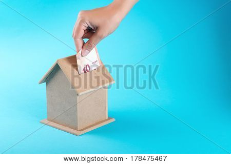 A female hand putting a ten euro into a money box. The concept of financial savings to buy house.