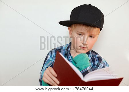 A child of primary school age doing homework.The boy in cap with blond hair and blue eyes does his homework holding a book reading new material. Back to school. Educational concept.