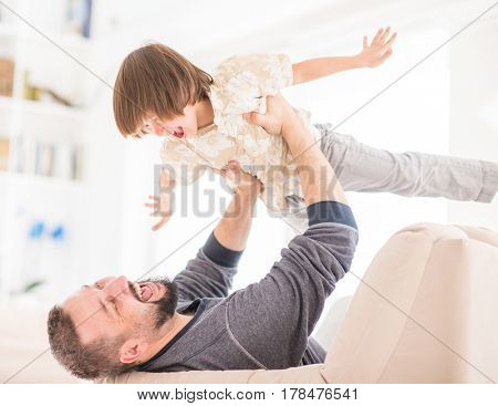 Child flying in father arms on sofa plane