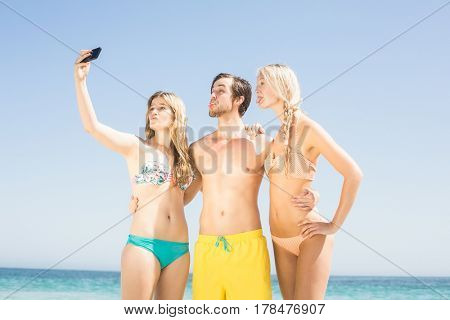 Young friends on the beach taking a selfie on mobile phone