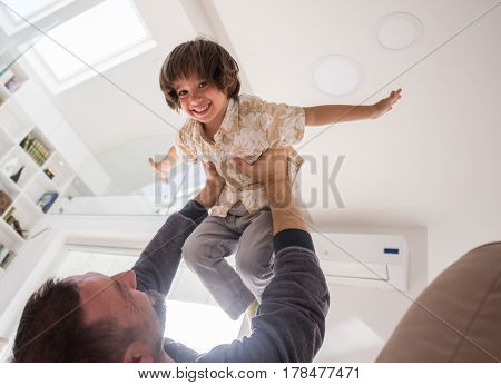 Little son playing with father on sofa with open outstretched arms