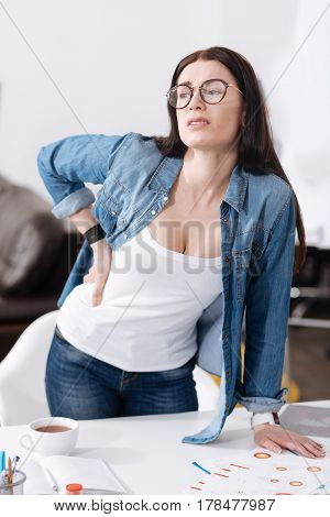 Be strong. Young female wearing jeans and shirt standing behind her workplace while looking sideways