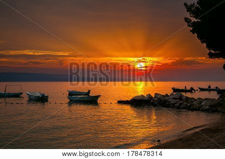 small boats with a sunset over the Adriatic sea on a background Brela Croatia