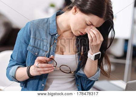Continue to work. Exhausted woman wearing jeans shirt holding glasses in right hand while touching her nose