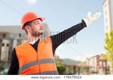 Low Angle Of Construction Worker Showing Something