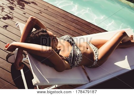 Fit woman lying on deck chair by the pool