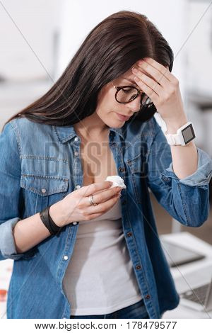 Need you. Young woman wearing smart watches looking downwards while keeping serviette in right hand