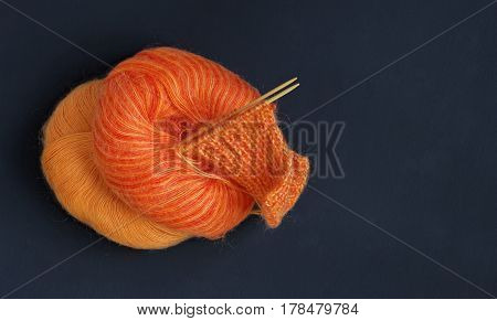 Knitting needles and orange multicolor colorful mohair soft warm winter yarn ball on the dark wooden table. The beginning of comfort knit cloth, creative craft artwork. Woman work place