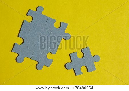 Jigsaw Puzzle pieces on yellow background horizontal with copy space
