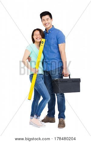 Young couple standing with spirit level measuring tool and tool box on white background