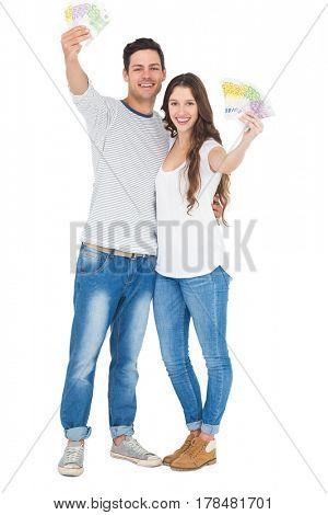 Happy couple holding money on white background