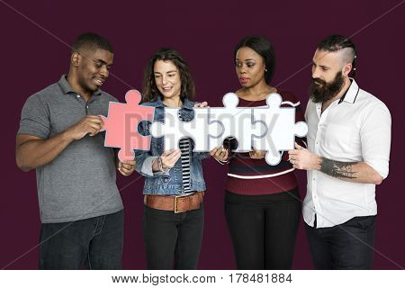 People are holding puzzle together