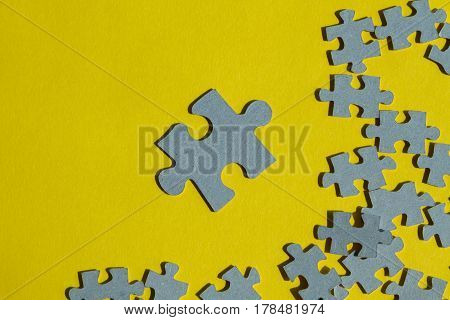 Jigsaw Puzzle pieces on yellow background one piece against a lot of pieces with copy space